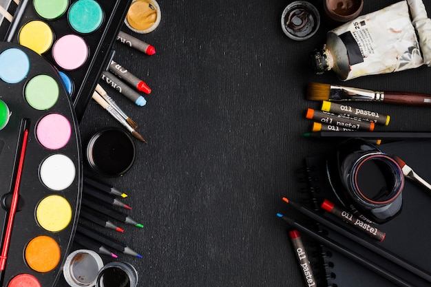 Plat lag verschillende borstels en kleurpotloden kopiëren ruimte Gratis Foto