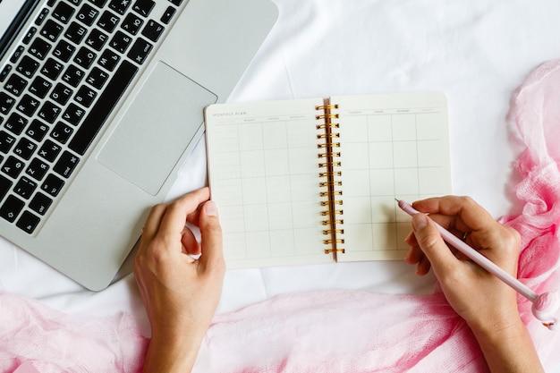 Plat lag werkruimte met laptop, vrouw hand schrijven pen in planner Premium Foto