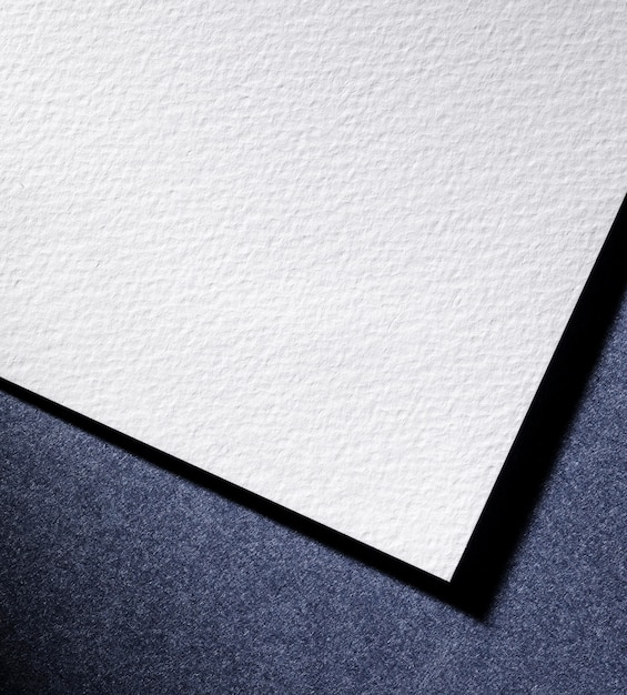 Plat lag wit papier op blauwe achtergrond Gratis Foto