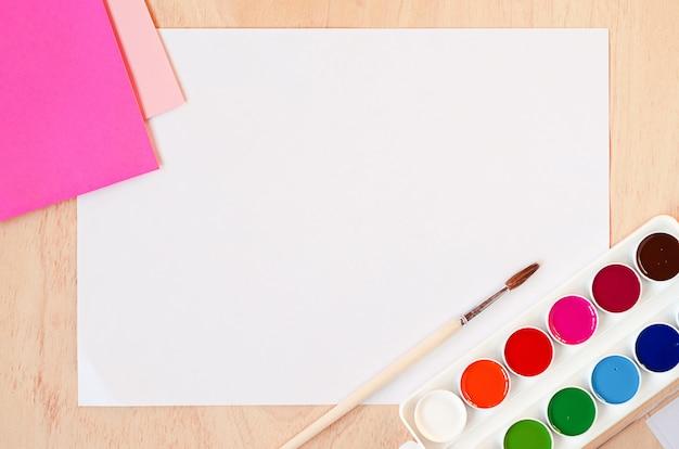 Plat lag wit vel papier, nieuwe aquarelverf en een set trendy roze kleuren op het palet. Premium Foto