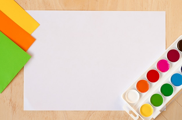 Plat lag wit vel papier, nieuwe aquarelverf, set trending herfstkleuren op houten tafel Premium Foto