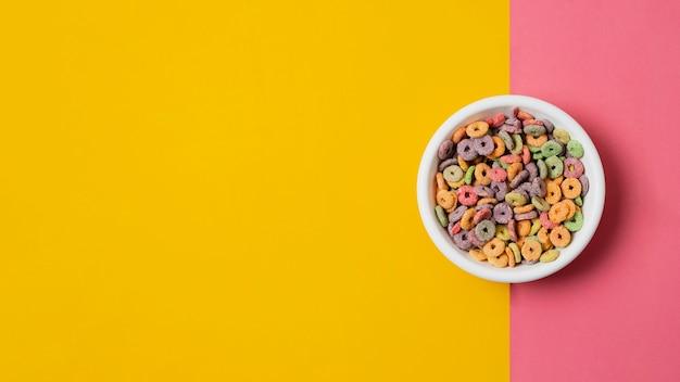 Plat lag witte kom met kleurrijke ontbijtgranen Gratis Foto