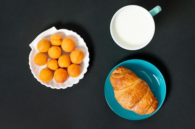 Plat leg croissant, melk en abrikozen op effen achtergrond Gratis Foto