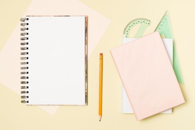 Plat leggen blanco notitieblok op lichte gele achtergrond Gratis Foto