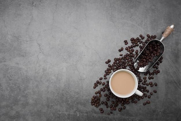 Plat leggen frame met koffiekopje en bonen Gratis Foto