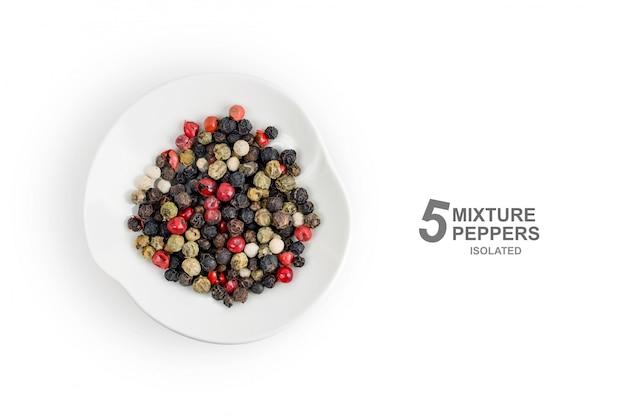 Plat leggen. geurig mengsel van vijf soorten willekeurig gekleurde paprika's in een plaat die op witte achtergrond wordt geïsoleerd. bovenaanzicht Premium Foto