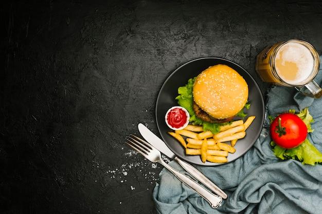 Plat leggen hamburger en gebraden gerechten op plaat met copyspace Gratis Foto