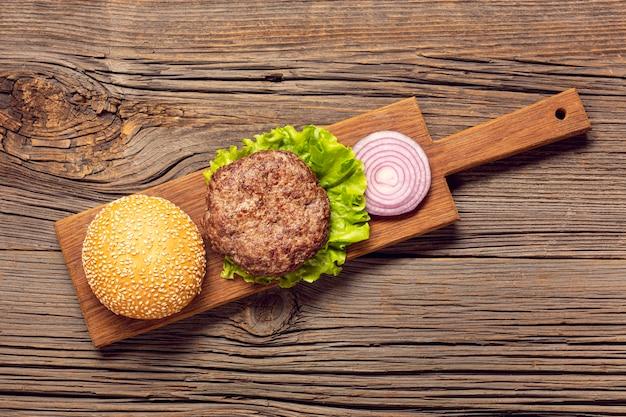 Plat leggen hamburger ingrediënten op een snijplank Gratis Foto