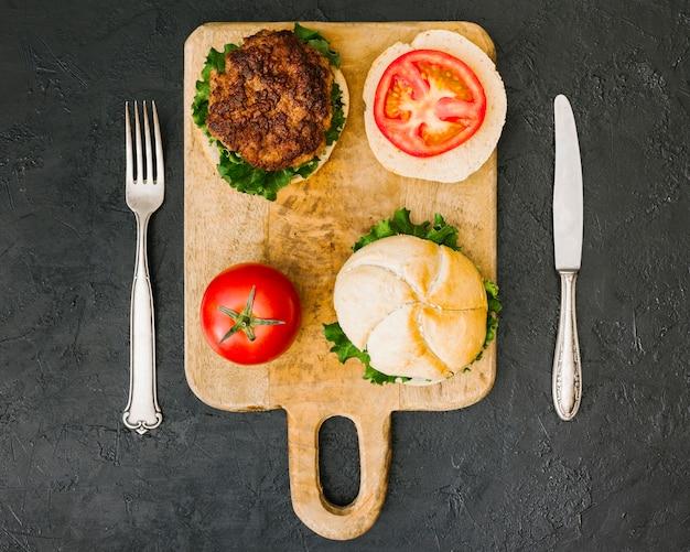 Plat leggen hamburger op houten bord met bestek Gratis Foto