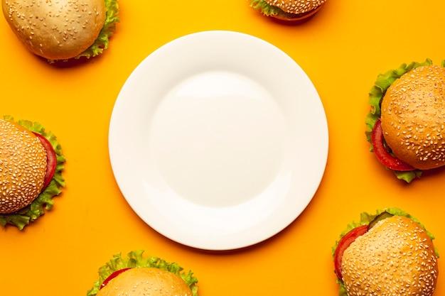 Plat leggen hamburgers met een lege plaat Gratis Foto
