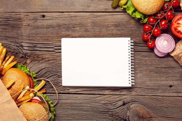 Plat leggen hamburgers met mock-up kladblok Gratis Foto