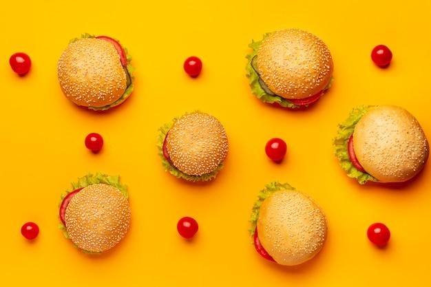 Plat leggen hamburgers met oranje achtergrond Gratis Foto