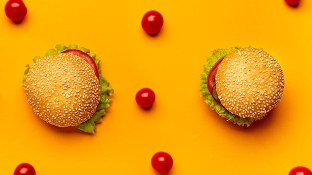 Plat leggen hamburgers op oranje achtergrond Gratis Foto
