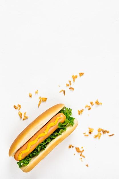 Plat leggen hotdog met knapperige ui Gratis Foto