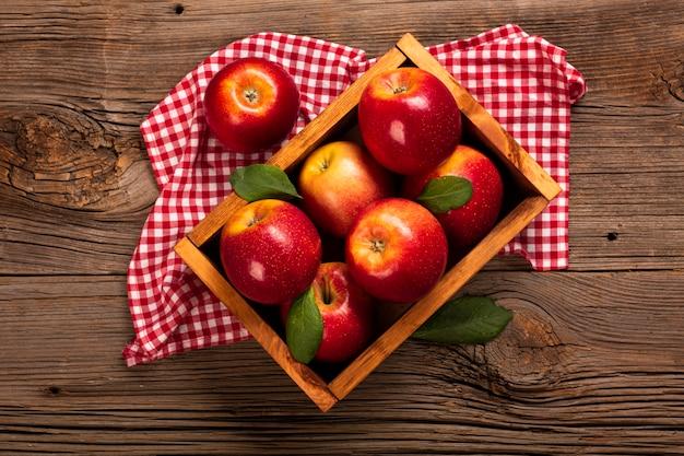 Plat leggen kist met rijpe appels op doek Gratis Foto