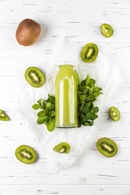 Plat leggen kiwi smoothie op witte houten tafel Gratis Foto