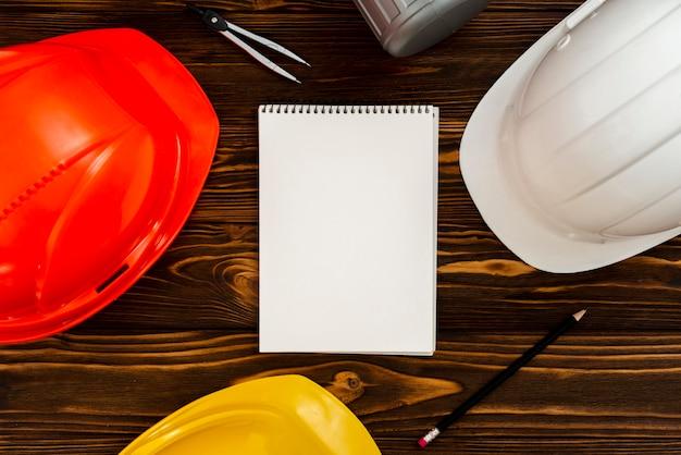 Plat leggen kladblok met bouw-helmen Gratis Foto