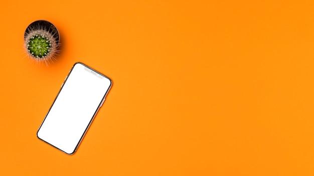 Plat leggen mockup smartphone met oranje achtergrond Gratis Foto