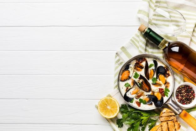 Plat leggen mosselen in wit en wijnsaus op tafelkleed met copyspace Gratis Foto