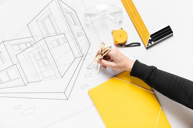 Plat leggen persoon bezig met architectonisch project Gratis Foto