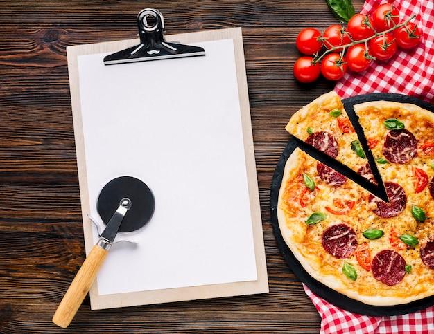 Plat leggen pizza samenstelling met klembord sjabloon Gratis Foto