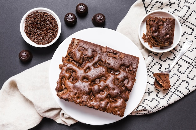 Plat leggen regeling met chocolade cake en snoepjes Gratis Foto