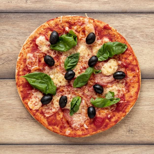 Plat leggen regeling met heerlijke pizza en houten achtergrond Gratis Foto