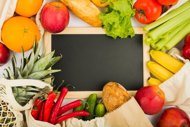 Plat leggen schoolbord met groenten en fruit in herbruikbare tassen Gratis Foto