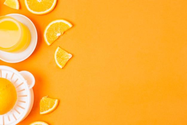 Plat leggen sinaasappelsap op oranje achtergrond met kopie ruimte Gratis Foto