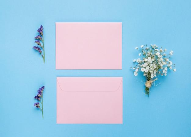 Plat leggen trouwkaarten naast bloemen Gratis Foto