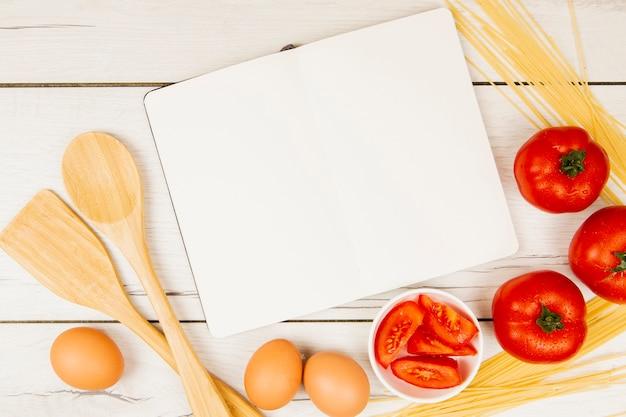 Plat leggen van boek en voedselingrediënten met kopie ruimte Gratis Foto