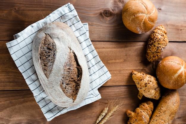 Plat leggen van brood op houten tafel Gratis Foto