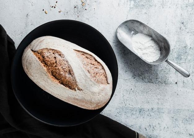 Plat leggen van brood op zwarte plaat Gratis Foto
