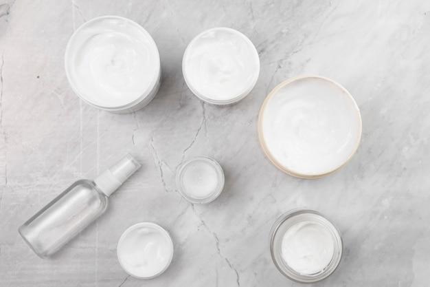 Plat leggen van crème dozen op marmeren achtergrond Gratis Foto