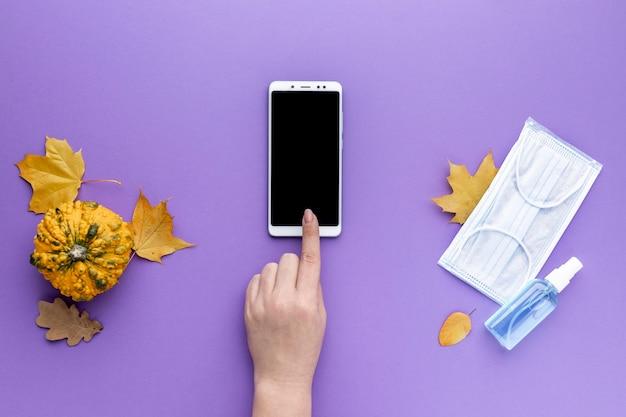 Plat leggen van de hand smartphone met medische masker en herfstbladeren Gratis Foto