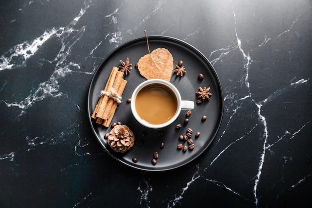 Plat leggen van dienblad met koffiekopje en kaneelstokjes Gratis Foto