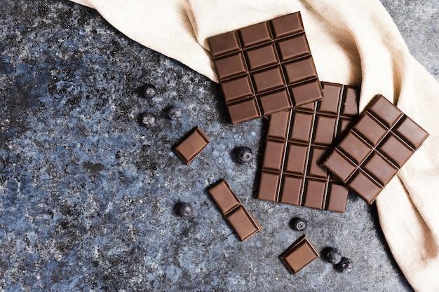Plat leggen van donkere chocolade op doek met bosbessen Gratis Foto