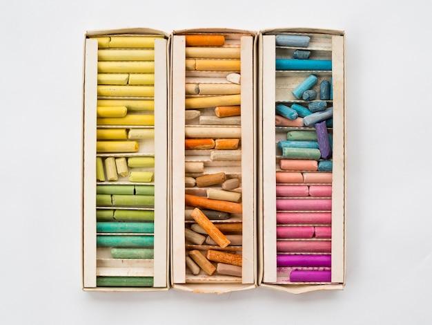 Plat leggen van doos met kleurrijk krijt Gratis Foto