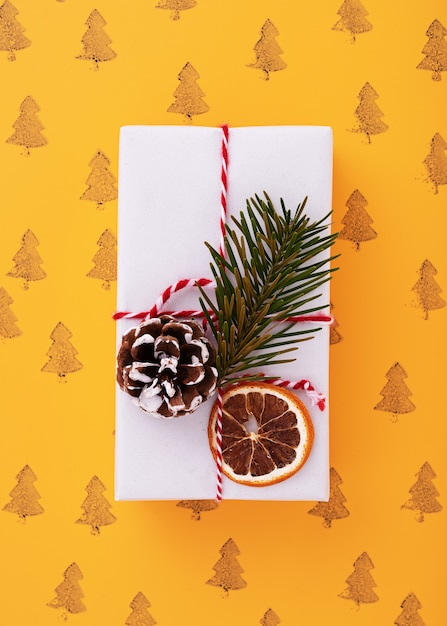Plat leggen van een witte versierde geschenkdoos, kerstbomen patroon in de oranje achtergrond Gratis Foto
