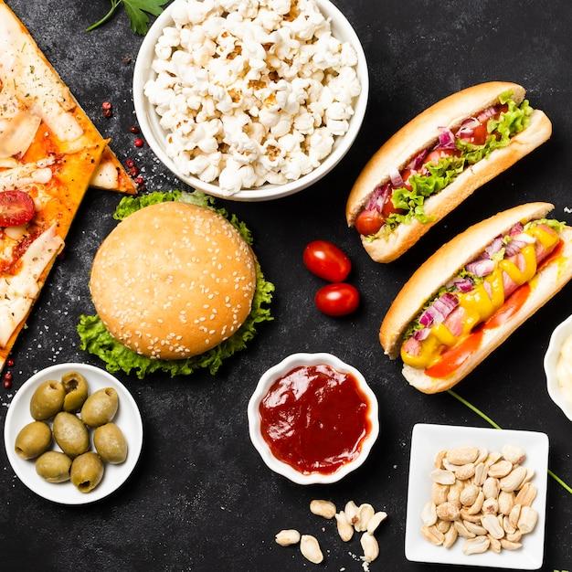 Plat leggen van fastfood op zwarte tafel Gratis Foto