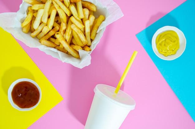 Plat leggen van friet en frisdrank op kleurrijke achtergrond Gratis Foto