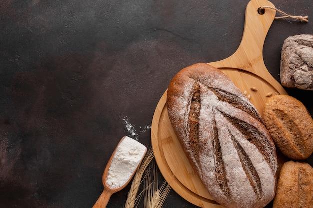 Plat leggen van gebakken brood van houten plank Gratis Foto
