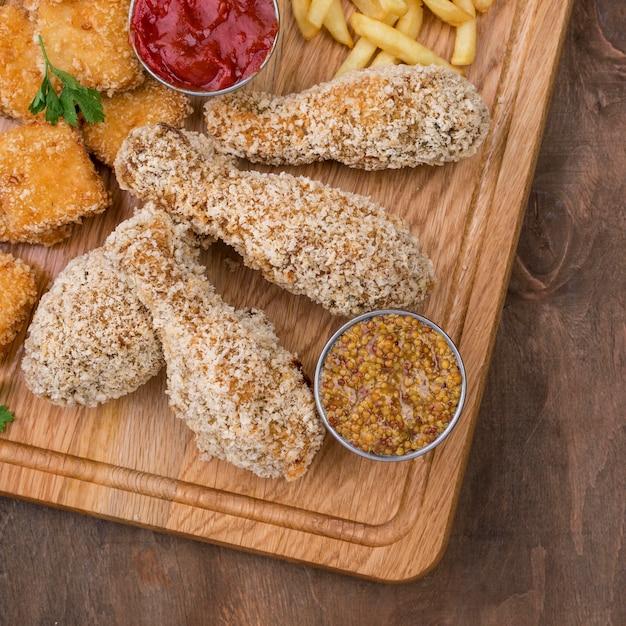 Plat leggen van gebakken kip met saus en frietjes Gratis Foto