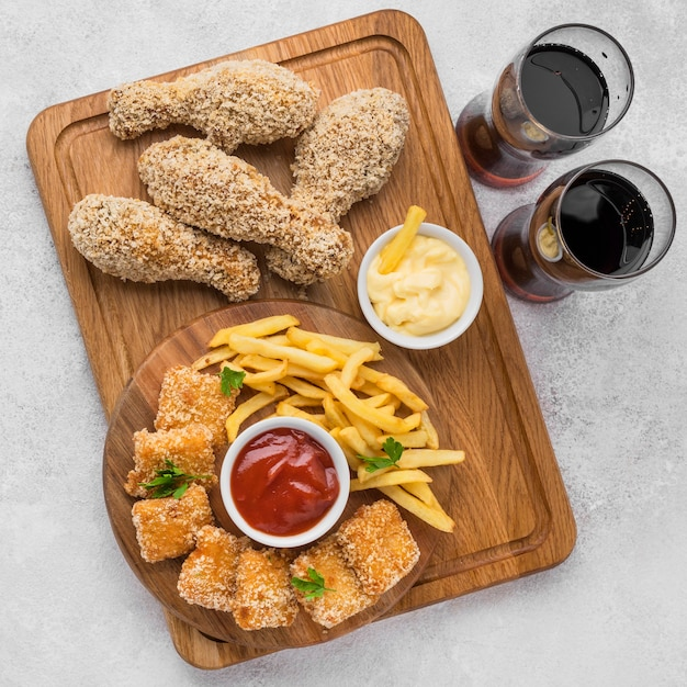 Plat leggen van gebakken kippenpoten en nuggets met koolzuurhoudende dranken en frietjes Gratis Foto