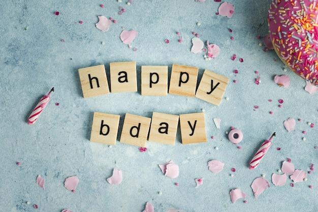 Plat leggen van gelukkige verjaardagswens in houten letters met donut Gratis Foto