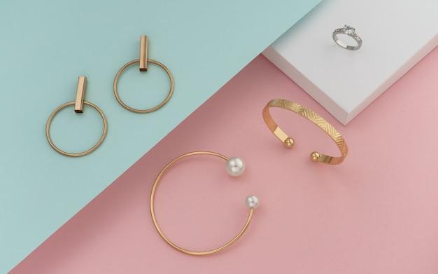 Plat leggen van gouden jewelries op pastel kleuren papier achtergrond Premium Foto