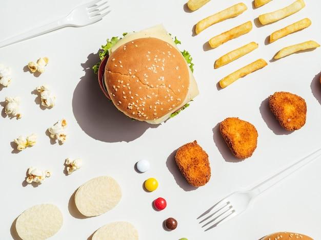 Plat leggen van hamburger, friet, nuggets en chips Gratis Foto