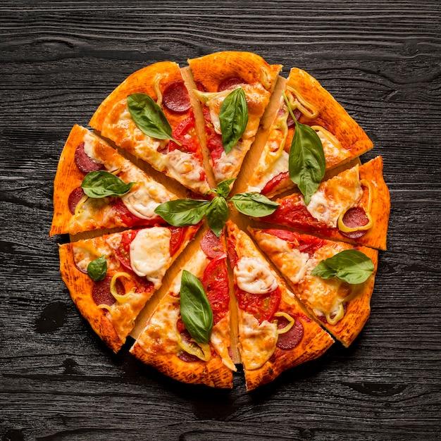 Plat leggen van heerlijke pizza concept op houten tafel Gratis Foto