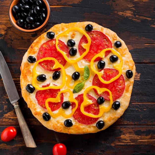 Plat leggen van heerlijke pizza op houten tafel Gratis Foto