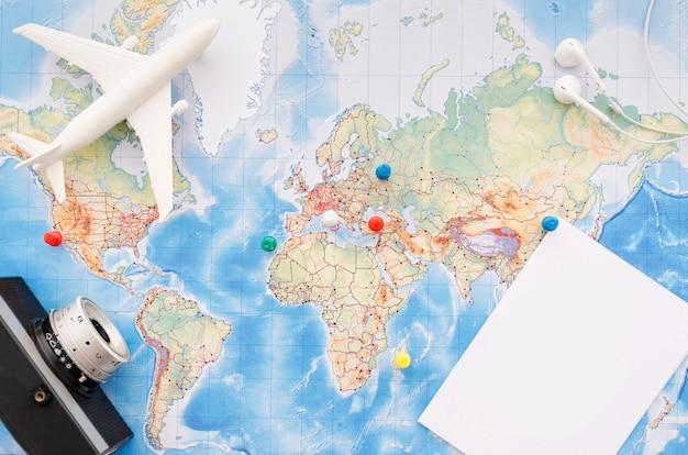 Plat leggen van kaart met camera en speelgoed vliegtuig Gratis Foto
